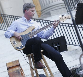 Chancellor Holden Thorp plays the electric bass outside Wilson Library for Monday night's Summer Jazz Workshop.