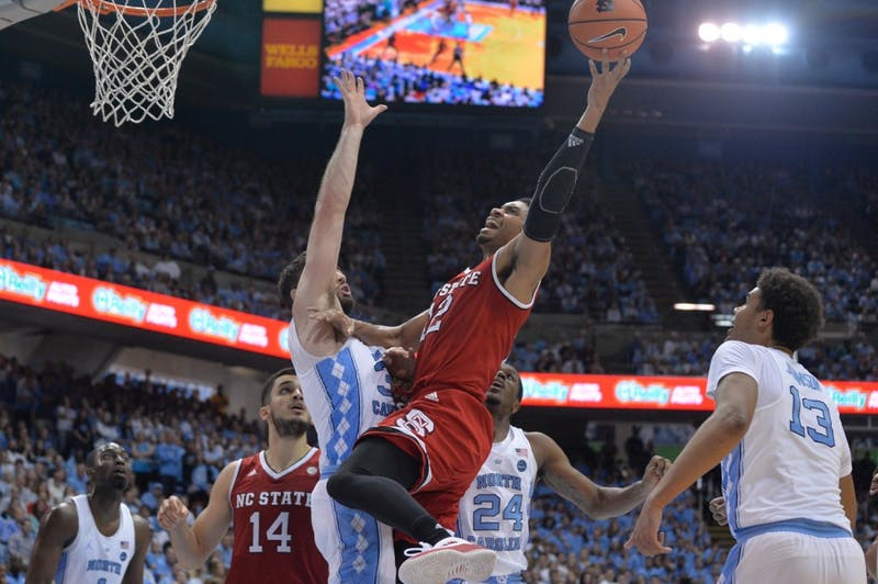 N.C. State forward Allerik Freeman (12) takes a layup over North Carolina guard Andrew Platek (3) during a Jan. 27 game in the Smith Center.