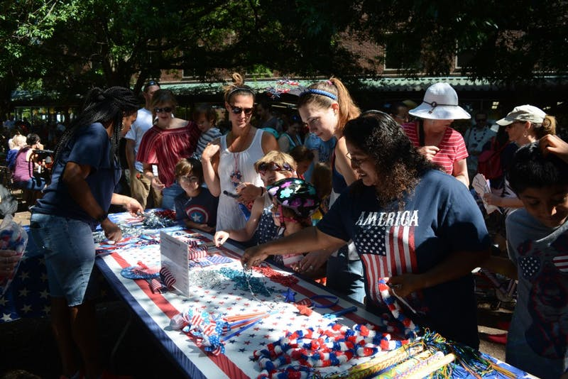 Carrboro residents browse the selections of flags, necklaces, and decorations for sale at the Fourth of July celebration.