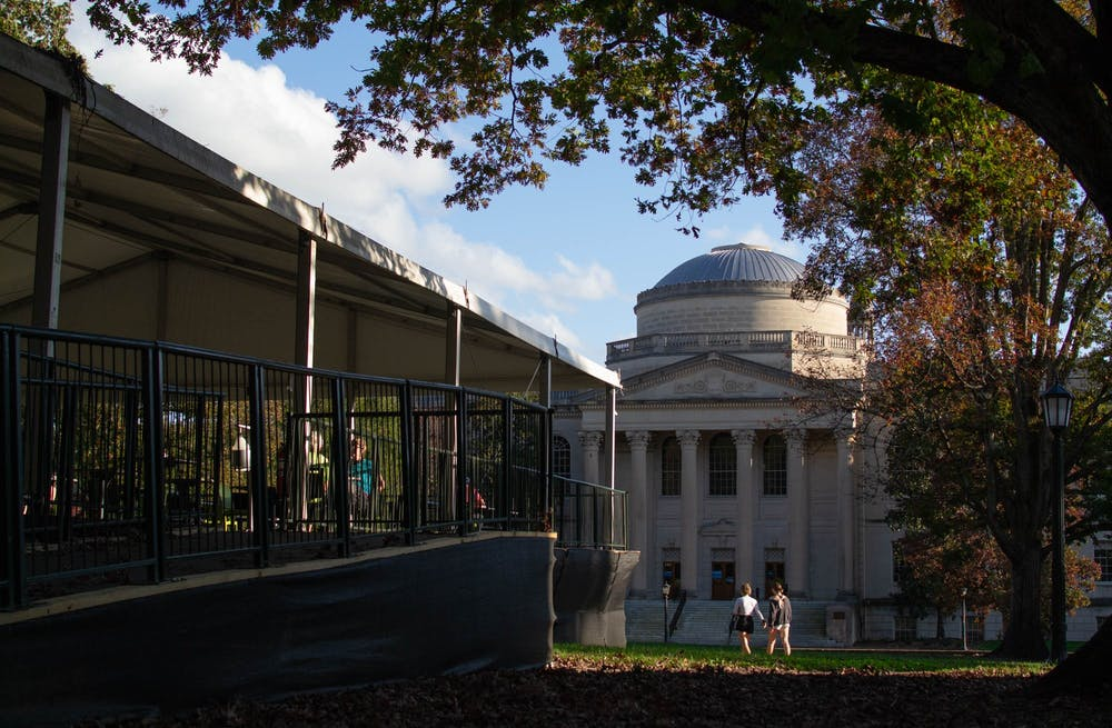 <p>Students study at the outdoor and socially-distanced study area the University built on Polk Place as other students walk past Wilson Library on Sunday, Nov. 15, 2020.</p>