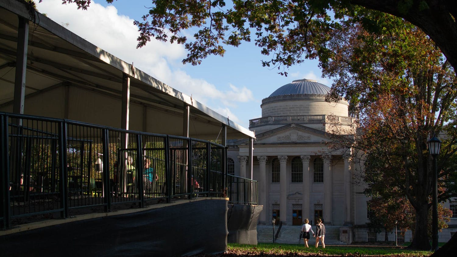 Students study at the outdoor and socially-distanced study area the University built on Polk Place as other students walk past Wilson Library on Sunday, Nov. 15, 2020.