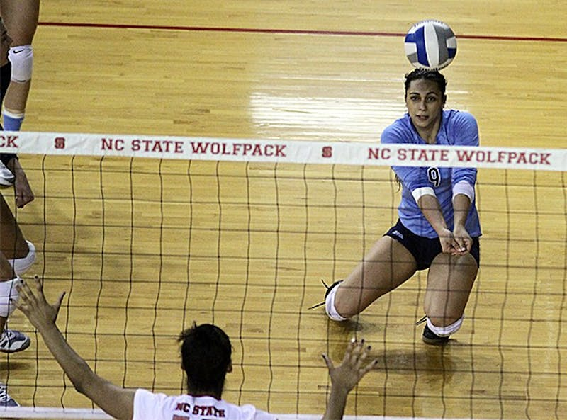 UNC junior defensive specialist Ece Taner (9) digs a ball in Wednesday night's game against N.C. State. UNC won the match 3-0.