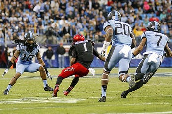 UNC defenders Tre Boston (10), Brandon Ellerbe (20), and Tim Scott (7) try to tackle Cincinnati's Ralph David Abernathy IV (1).