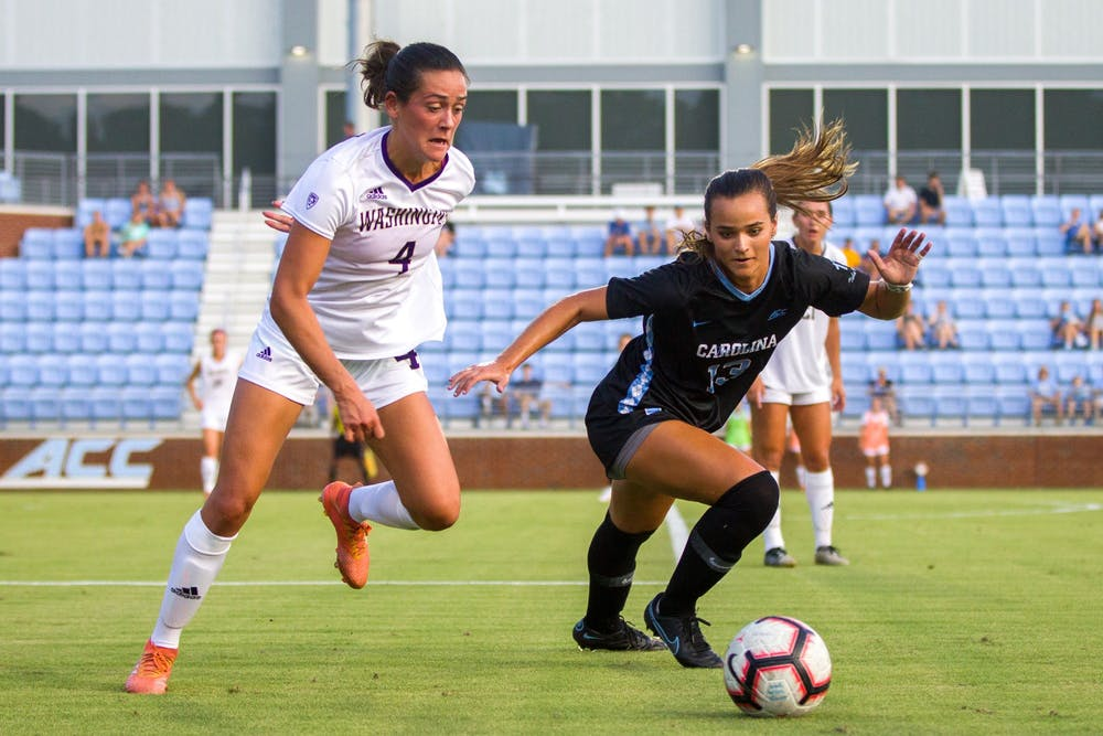 <p>Junior Forward Isabel Cox (13) attempts to regain the ball from a Washington Husky during UNC's women's soccer matchup on Thursday, Aug. 19, 2021, at Dorrance Field in Chapel Hill, NC. The Tar Heels won 4-1.</p>