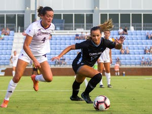 Junior Forward Isabel Cox (13) attempts to regain the ball from a Washington Husky during UNC's women's soccer matchup on Thursday, Aug. 19, 2021, at Dorrance Field in Chapel Hill, NC. The Tar Heels won 4-1.