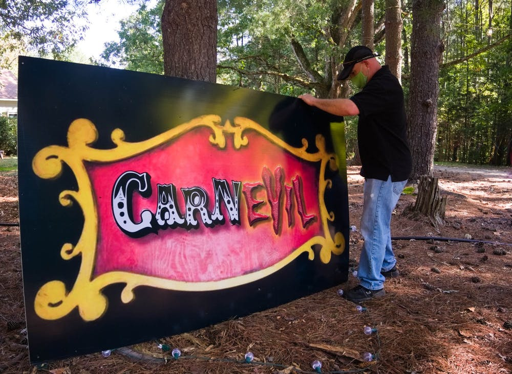 Dennis DeFrancesco places a sign at the Haunted Hills Terror Drive on Wednesday, Oct. 7, 2020. DeFranceso and his wife, Christie Cook, host the Haunted Hills Terror Drive.