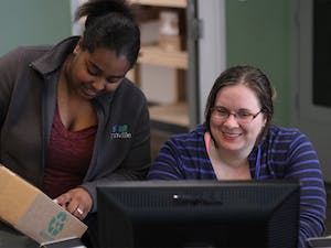 Shavon Flowers (left) and Meghan Eisenhardt, a sophomore undecided major from Greensboro, work at Granville Towers. Both have worked there since September 2013, Eisenhardt as a desk attendant and Flowers as a receptionist.