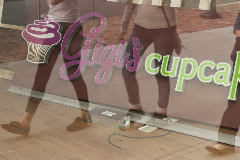 UNC students walk by  the window display of Gigi's Cupcakes on West Franklin Street,. Gigi's closed permanently on Saturday due to low sales.