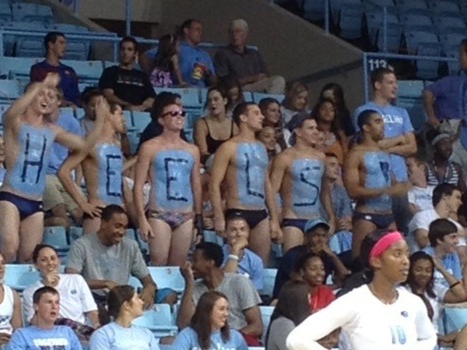 Members of the UNC men's swim team cheer on the volleyball team Friday night at Carmichael Arena.