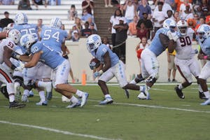 Running back Michael Carter (8) carries the ball against Virginia on Oct. 14 in Kenan Memorial Stadium.