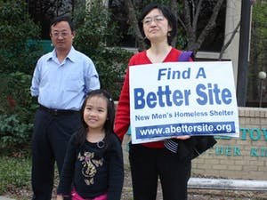 Hongping Dai, Clarissa Zuo and Sue Xu ( L to R) protest outside the Chapel Hill Town Hall tonight before the meeting regarding the new IFC shelter on Martin Luther King Jr. Blvd began.