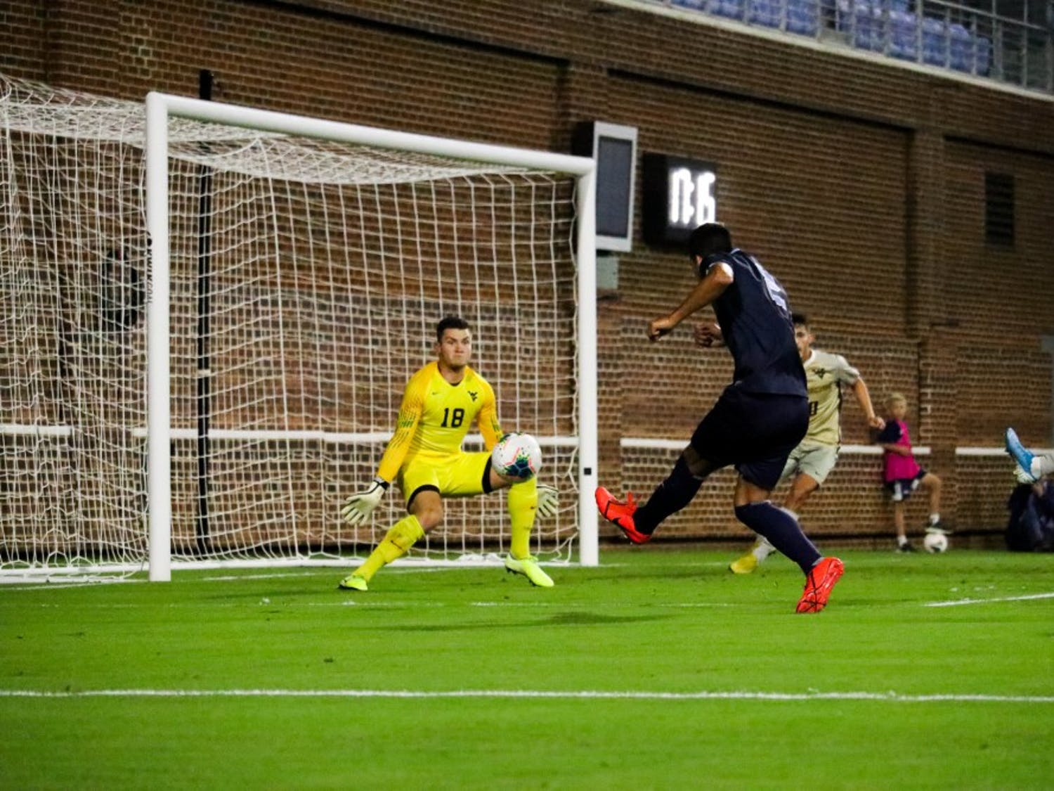 Senior midfielder Mauricio Pineda (2) scores a goal against WVU goalie Steven Tekesky (18) in the first half during the team's 3-1 victory over West Virginia on Tuesday, Oct. 8, 2019. Pineda scored two goals during the win.