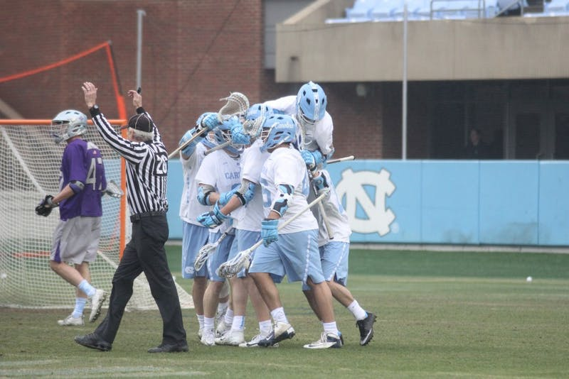 The North Carolina men's lacrosse team celebrates a goal against Furman on Feb. 10 in Kenan Stadium.