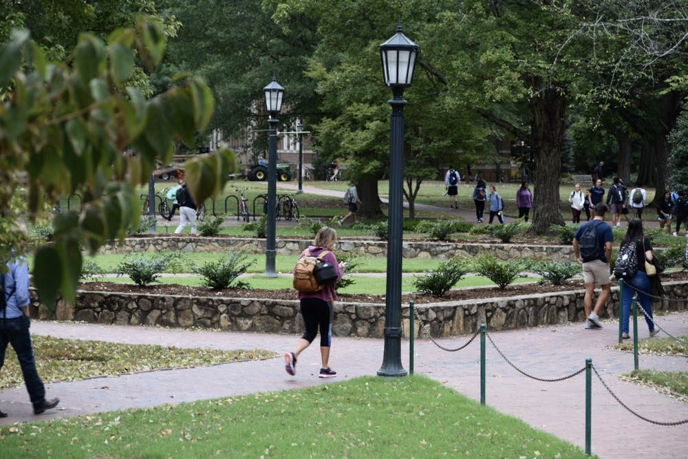 Students traverse Polk Place on Tuesday, Oct. 8, 2019. Changes to UNC's absence policies have stirred concerns within the student population.