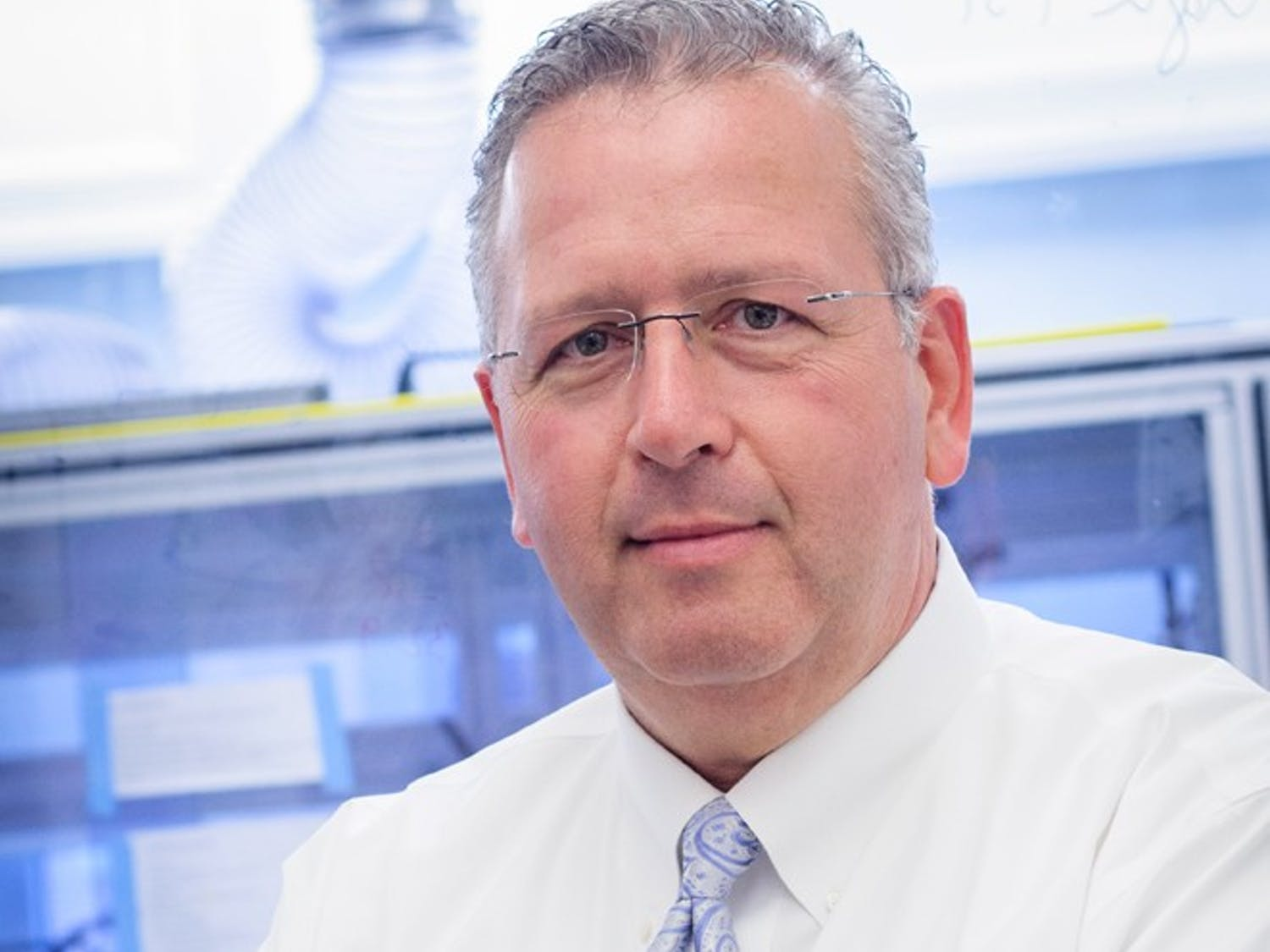 Professor Joseph DeSimone pictured in front of the roll-to-roll particle-fabrication unit housed at UNC-Chapel Hill's Caudill Labs. Roll-to-roll fabrication technology is used in the manufacture of vaccines and medicines.