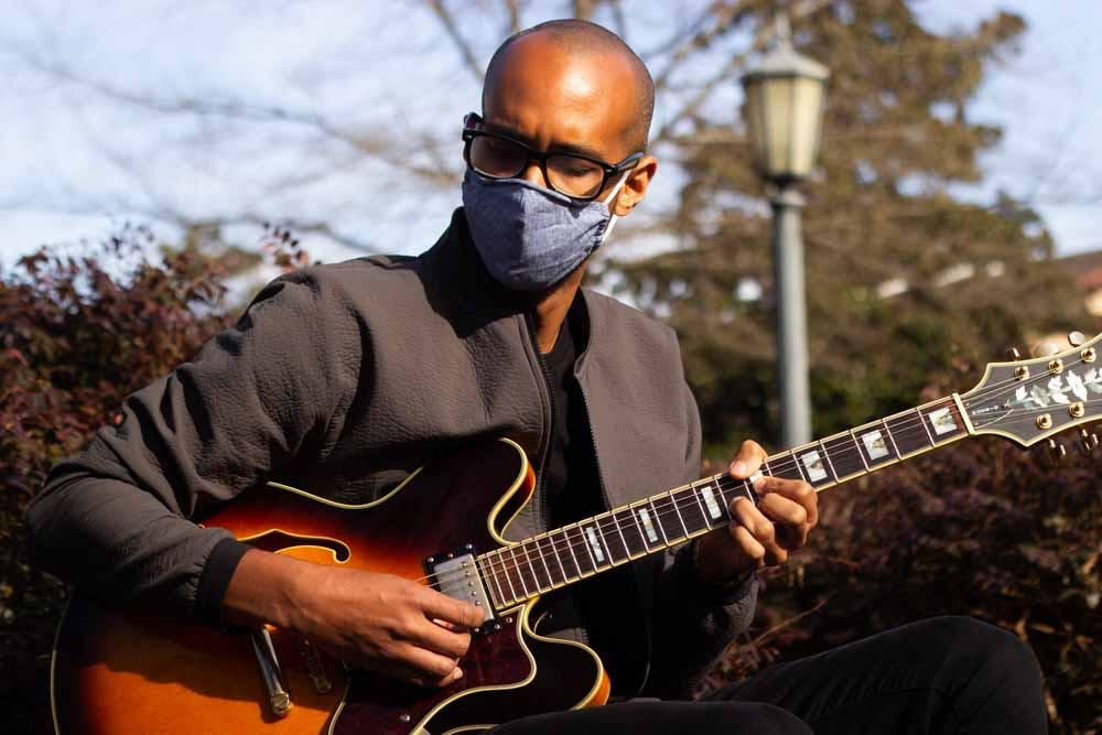Musician Keenan Jenkins, or XOXOK, plays guitar at the Old Well on Friday, March 5th, 2021.