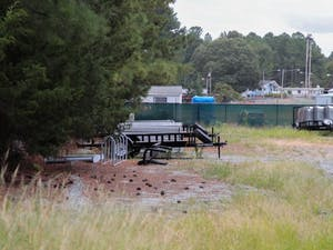A large cube wrapped in a tarp behind a UNC Facilities area near Horace Williams Airport.