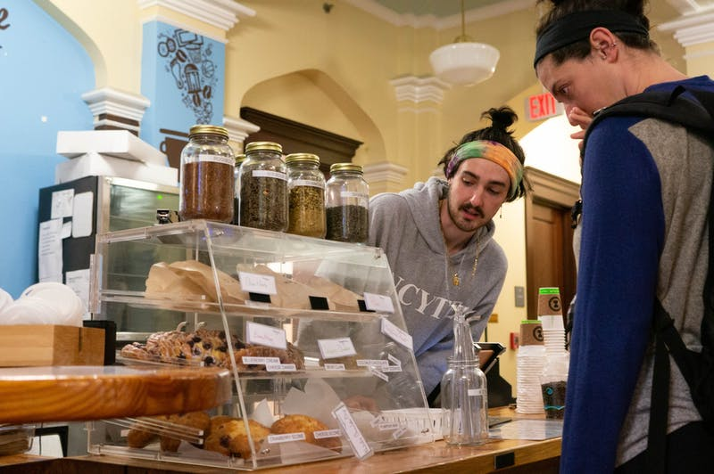 John Vance, a junior at UNC and barista at the student-run Meantime Coffee Company, helps a customer select a pastry in the Campus Y on Thursday, Jan 16, 2020. 100% of profits from Meantime are going to help the wildfire crisis in Australia.