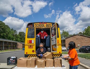 Volunteers load food into the back of a school bus as part of the Food for Students program. Chapel Hill-Carrboro City Schools created the program in March to help students gain easy access to meals and bridge hardship gaps caused by remote schooling. Photo Courtesy of Christine Cotton.