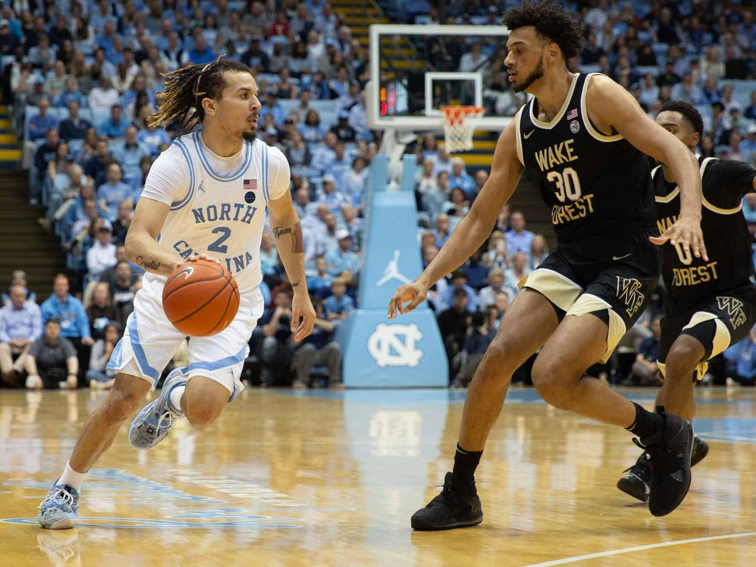 First-year guard Cole Anthony (2) runs down the court as Wake Forest junior center Olivier Sarr (30) tries to block him during a game in the Smith Center on Tuesday, March 3, 2020. The Tar Heels won 93-83 against the Demon Deacons during senior night.