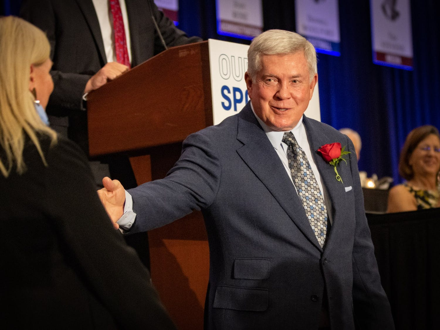 Inductee Mack Brown waves his wife over as he is introduced at the North Carolina Sports Hall of Fame induction ceremony Friday.