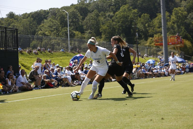 Bridgette Andrzejewski (8) turns against UCF defender Aubrey Megrath (3).