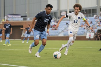 UNC Junior Raul Aguilera (28) dribbling towards the goal hoping to best Duke's senior captain Brandon Williamson (19) on the defensive side. UNC lost to Duke 2-3.