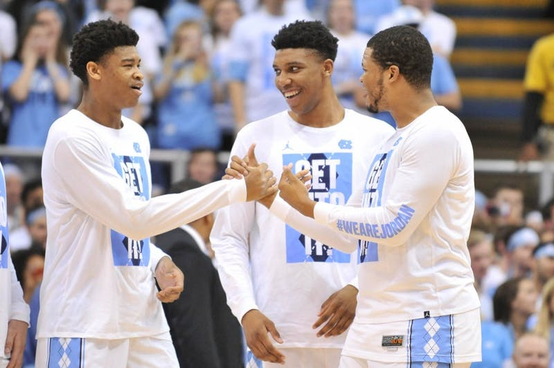 Seniors Isaiah Hicks (left) and Kennedy Meeks (right) celebrate during the senior night ceremonies before the game.