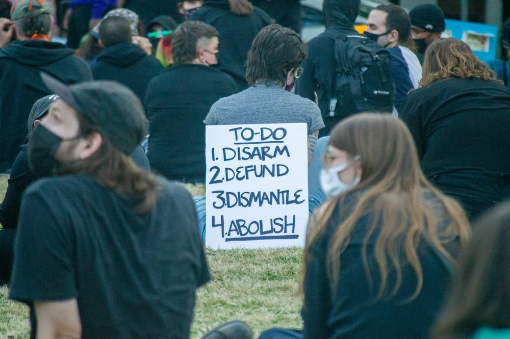 <p>A sign calling for action leans against an attendee at a community organized vigil in memory of Daunte Wright and Jaida Peterson. The vigil took place in Moore Square Park in downtown Raleigh on Sunday Apr. 18, 2021.</p>