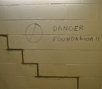 """In the ground floor of a Hamilton stairwell, a strange """"Danger!"""" sign is written next to cracks in the foundation."""