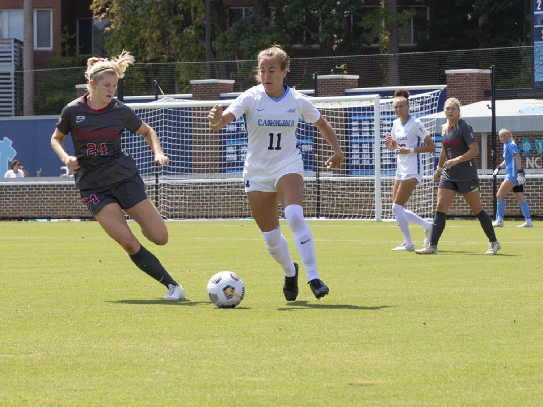 UNC freshman midfielder Lauren Wrigley (11) chases the ball against Stanford senior forward Abby Gruebel (24) on Sept. 5, 2021. UNC won in overtime 2-1.