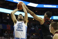 Cardinal graduate guard Christen Cunningham (1) attempts to block a shot by Tar Heel senior forward Luke Maye (32) in the quarterfinals of the ACC tournament on Thursday, March 14, 2019 at the Spectrum Center in Charlotte, N.C. UNC defeated Louisville 83-70 to advance to the semifinals.