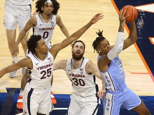 North Carolina forward Armando Bacot (5) grabs the rebound next to Virginia forward Jay Huff (30) and Virginia guard Trey Murphy III (25) during the game Saturday in Charlottesville. Photo courtesy of Andrew Shurtleff/The Daily Progress.