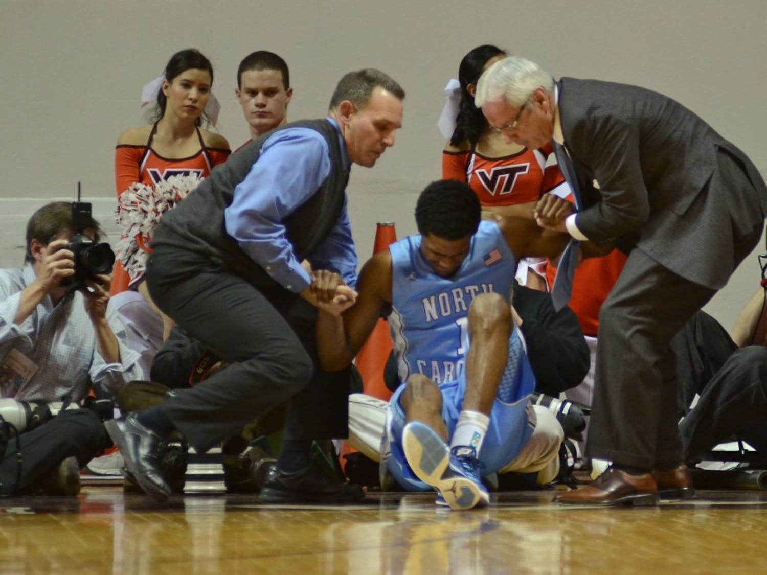 Carolina guard Dexter Strickland was helped up by head coach Roy Williams and head athletic trainer Chris Hirth in the second half of Carolina's 82-68 win over Virginia Tech Thursday night in Cassell Coliseum.