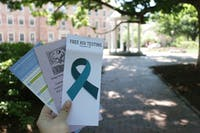 A UNC student holds three sexual education pamphlets in front of the Old Well in the Upper Quad on Tuesday.