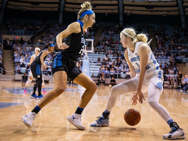 UNC senior guard Taylor Koenen (1) dribbles past Duke University graduate guard Haley Gorecki (2) in Carmichael Arena on Sunday, March 1, 2020. The Blue Devils beat the Tar Heels 73-54.
