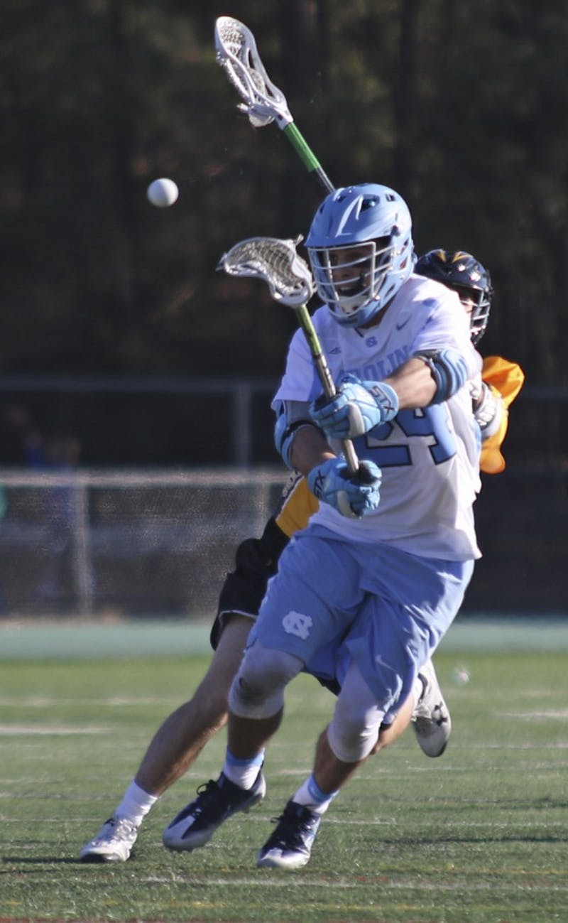 UNC midfielder Stephen Kelly (24) fires a shot after winning a face-off against UMBC on Saturday at Cardinal Gibbons High School in Raleigh.