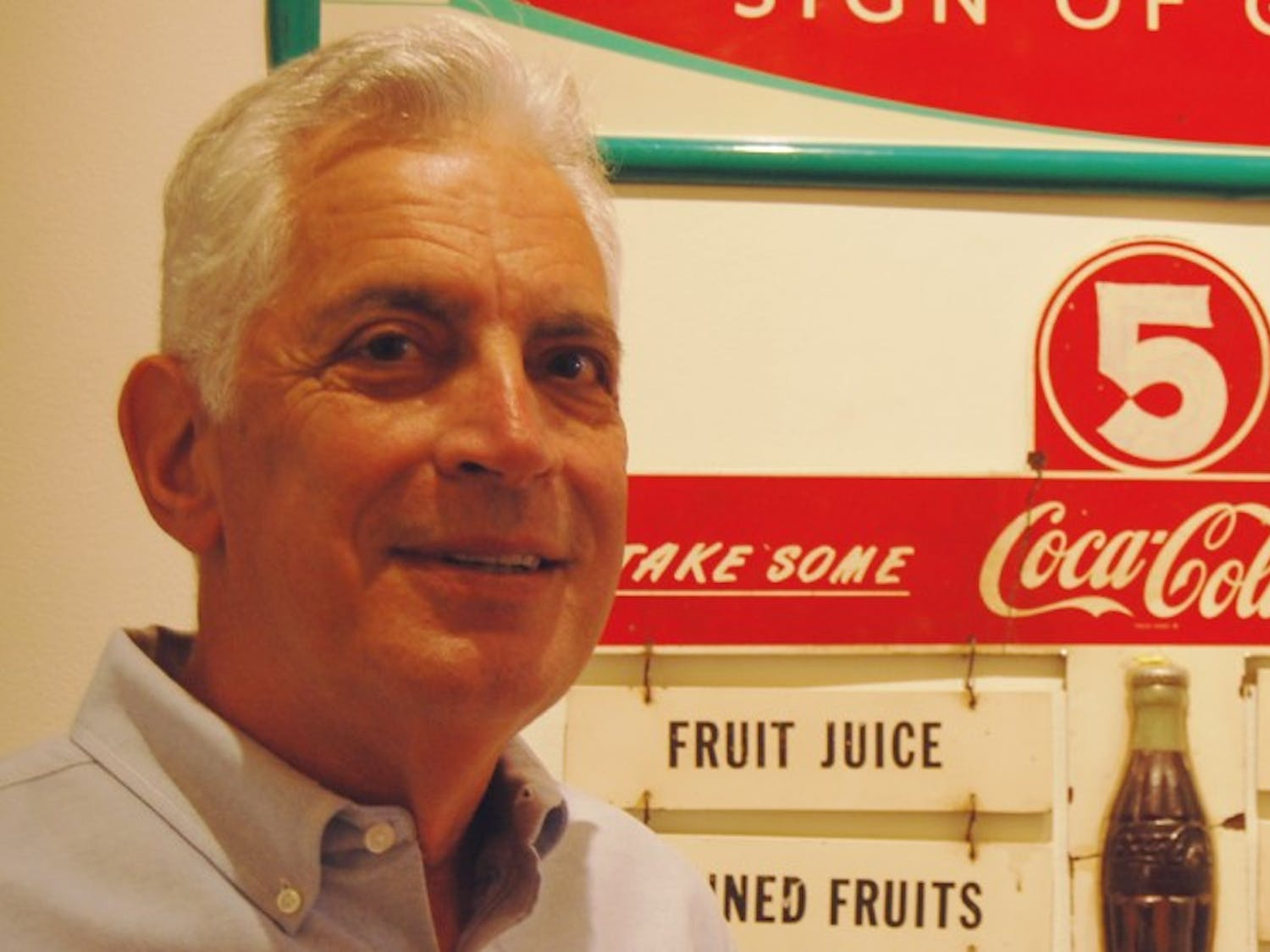 Stephen Rich, a former executive at the Coke corporation, with Coke memorabilia. The artifacts are displayed throughout The Love House and Hutchins Forum.