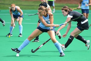 Sophie Rudolph prepares to send one for a ride as Sinead Loughran looks on in Sunday's match with Davidson.  Second ranked North Carolina netted four goals in the first eight minutes of the game.