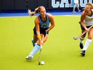 Senior midfielder Ashley Hoffman (13) sprints with the ball in her possession against Wake Forest defender Veerle Bos (17) in UNC's winning match of 5-1 on Saturday afternoon in the Karen Shelton Stadium.