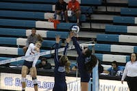 Uva player spikes past UNC defenders Ava Bell and Hunter Atherton on Sunday October 14th in Carmichael Arena.