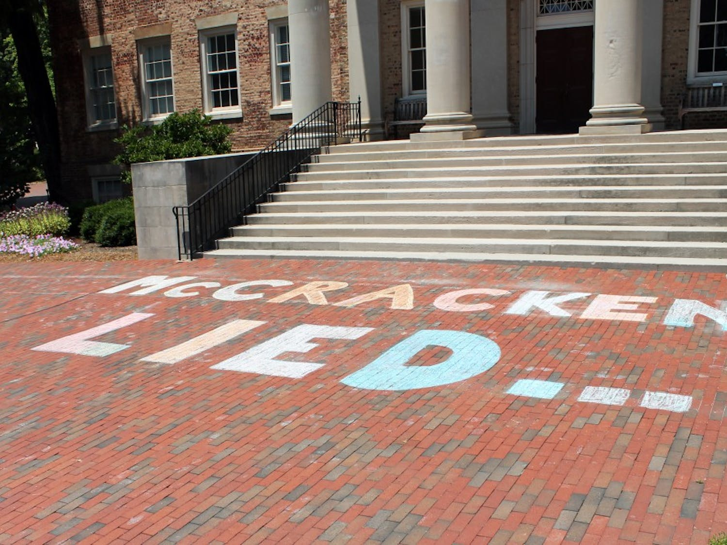 """On July 11, protestors chalked """"McCracken Lied"""" on the bricks in front of South Building."""