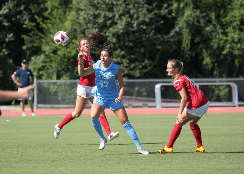 Redshirt senior midfielder Alex Kimball fights for the ball against two Wolfpack defenders during UNC's 3-2 exhibition win over N.C. State on Aug. 9 in Raleigh.