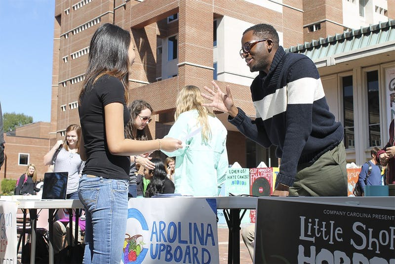 Roderick Gladney (right) helps recruit new members during Carolina Cupboard's opening week of events in the Pit on Monday .