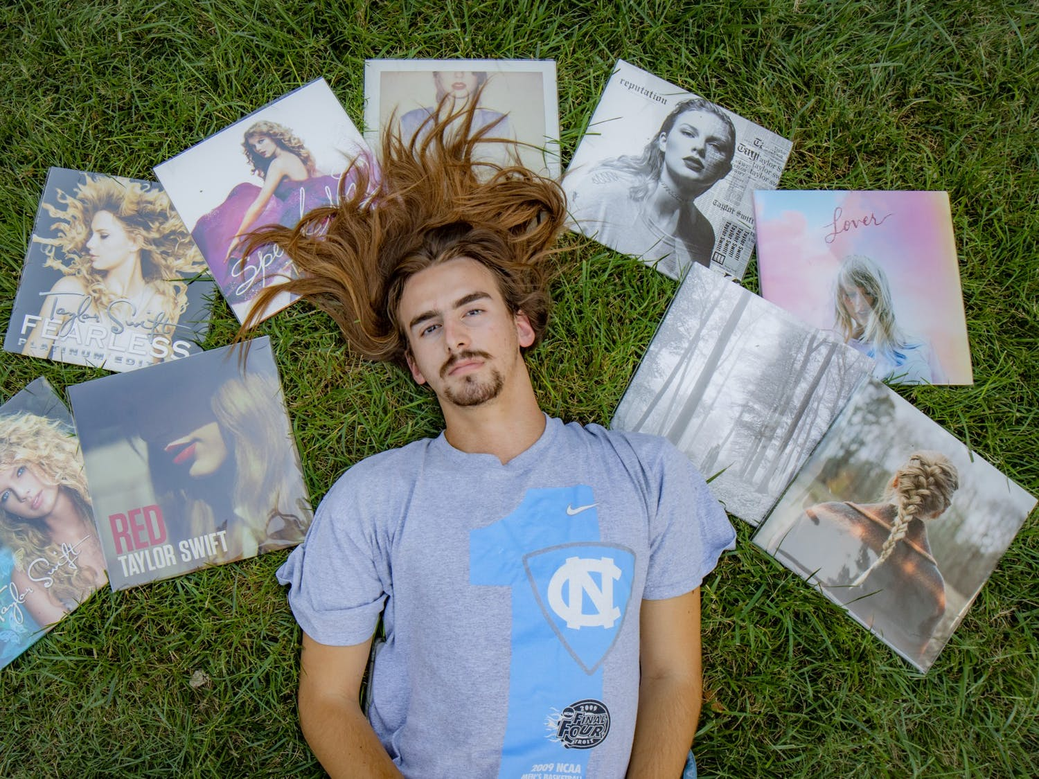 DTH Photo Illustration. Assistant Photo Editor and Resident Taylor Swift Expert Ira Wilder lays in the grass with his collection of Taylor Swift vinyls.