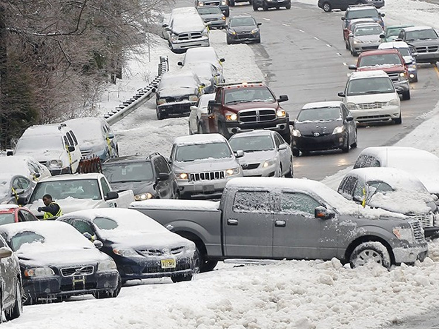 Police and wrecker crews work to remove dozens of vehicles that were either parked or abandoned on Glenwood Ave. just west of Crabtree Valley Mall in Raleigh, N.C., on Thursday, Feb. 13, 2014. (Chris Seward/Raleigh News & Observer/MCT)