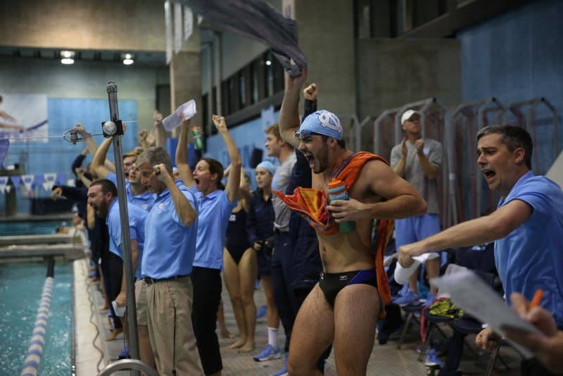 Patrick Cusick waves his shirt and cheers with the rest of the swim team after Sophie Lindner's victory in the women's 100 yard butterfly at the home swim meet vs South Carolina on Friday, Oct. 26 2018.