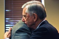 Tom Ross, current UNC-system president, hugs a colleague after a news conference Friday. Ross announced he would be stepping down in January 2016.