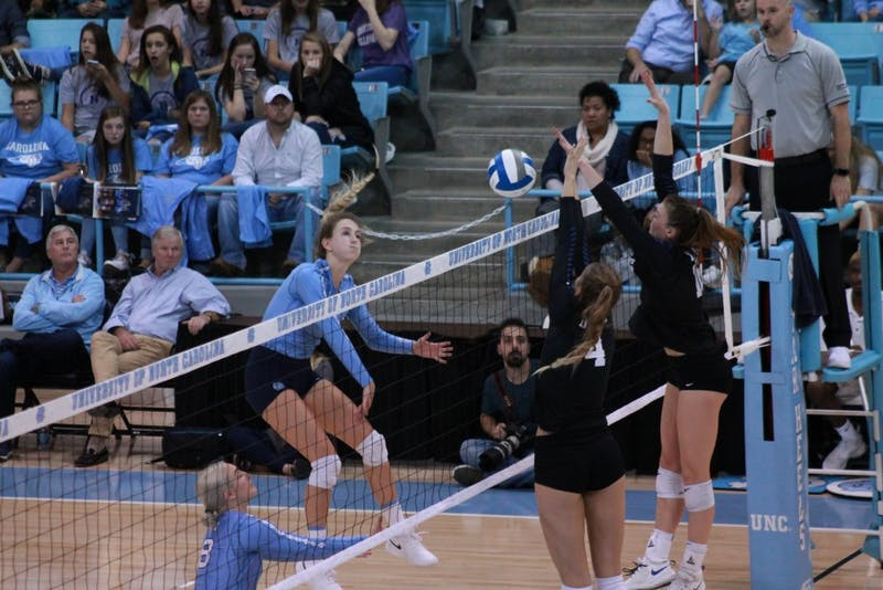 UNC junior Skylar Wine (6) spies the ball over two Duke players during a set in their 3-0 loss to Duke in Carmichael Arena on Friday, Nov. 2, 2018.