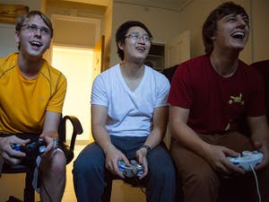 """Freshman Jimmy Messmer, left, graduate student Weilin Zou, and senior Tyler Crews play the video game Super Smash Bros. in an Everett dorm room. Inspired by the 2013 film """"Super Smash Bros.,"""" members compete against one another in each others dorm rooms, referred to as """"smash houses"""" by the group, and in common areas where a television is present."""